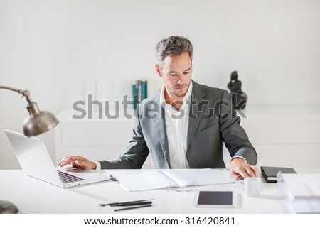 A middle age businessman with grey hair and beard wearing a grey suit and white shirt is working on his computer in his luminous office surrounded by his notebook, glasses, tablet and cup of coffee. - stock photo