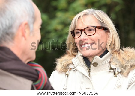 A middle age couple in a park. - stock photo