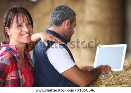 A middle age couple in their farm. - stock photo