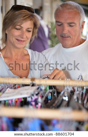 A middle age couple shopping for clothes. - stock photo