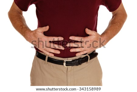 A middle age man in a burgundy t-shirt holding hid stomach for pain in acloseup body part image for white background. - stock photo