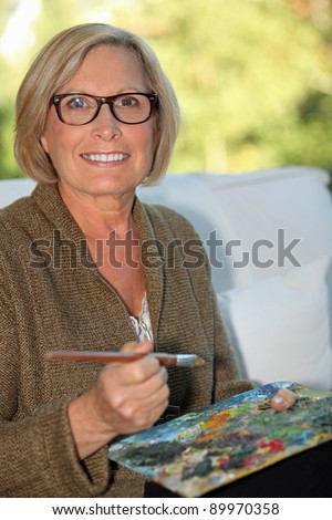 A middle age woman painting. - stock photo