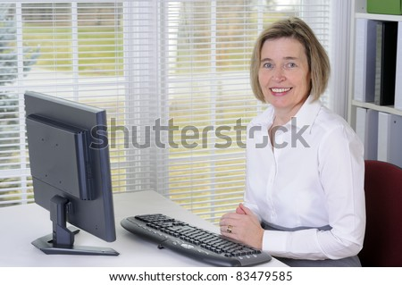 A Middle Age Woman Working With A Computer In Her Office - stock photo