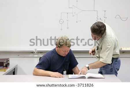 A middle aged adult education student getting help from his teacher. - stock photo