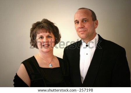 A middle aged couple formally dressed.  Soft lighting. - stock photo