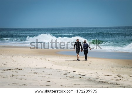 A middle aged couple goes for a walk along the beach on Long Beach Island along the Jersey shore. - stock photo