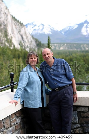 A middle aged couple on a scenic tour of the Rocky Mountains of Canada. - stock photo