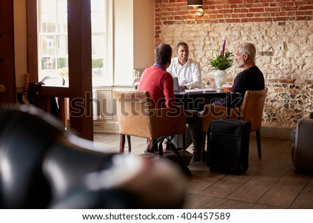 A middle aged gay male couple check in at a boutique hotel - stock photo
