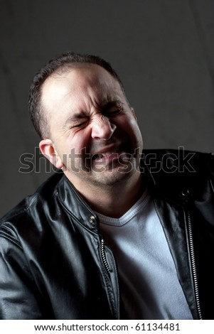 A middle aged man experiences extreme pain from a bad migraine or headache. - stock photo
