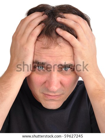 A middle aged man has stress and worry and he is holding his hands on his head, in his hair. Use it for a headache, money trouble or security concept. - stock photo