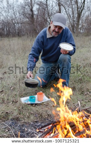 A middle-aged man is going to pour tea in cups before the fire