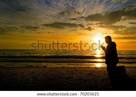 A middle aged man kneeling and praying at the beach with a glorious sunset in the background. - stock photo