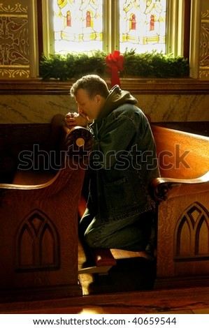 A middle-aged man praying in a church at Christmas time. - stock photo