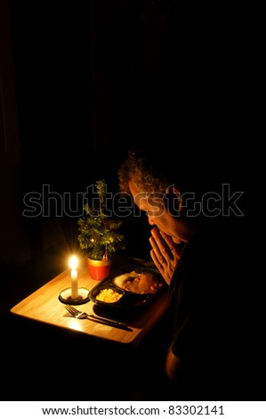 A middle-aged man praying over a TV dinner at Christmas time. - stock photo