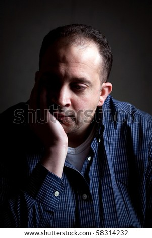 A middle aged man with a contemplative look on his face.  He could be worried or depressed about something.
