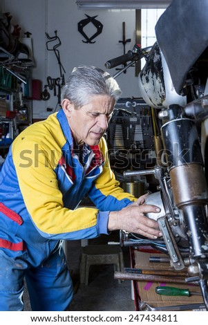 a middle aged mechanic is repairing the engine of a classic motorcycle in process of restoration at his workshop - focus on the man face