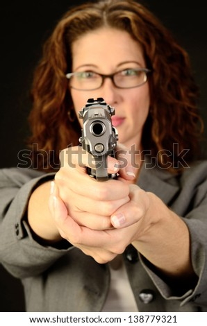 A middle aged, white, female business woman or teacher holds a semi automatic pistol during this dark photo shoot against black - stock photo