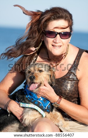 A middle aged woman by the ocean holding a cute mixed breed Beagle Yorkshire terrier dog also referred to as a Borkie. - stock photo