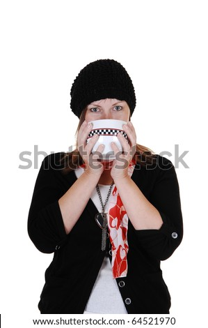 A middle aged woman drinking from a big cup some hot tee, with a sweater, scarf and hat on.