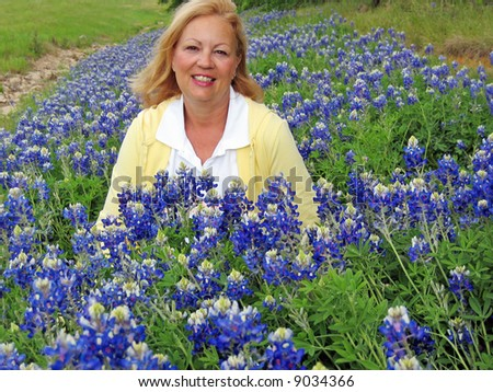 A middle-aged woman is shown amongst a field of bluebonnet flowers - stock photo