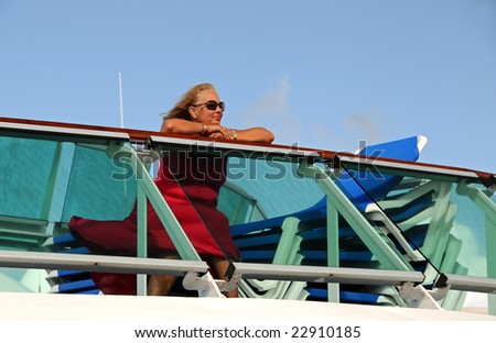 A middle-aged woman sits on the top deck of a cruise ship - stock photo