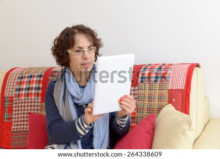 a middle aged woman with a digital tablet on the sofa - stock photo