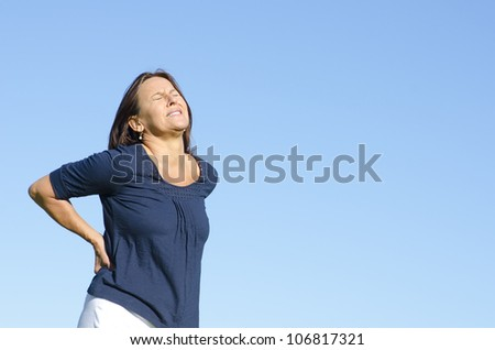 A middle aged woman with back ache problems and a painful facial expression. Isolated with clear blue sky as background and copy space. - stock photo