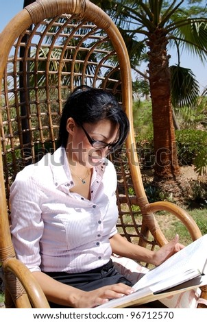 A middle eastern female with a book in the garden - stock photo