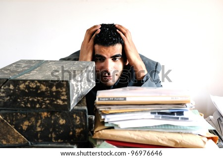 A middle eastern male with piles of papers and files - stock photo