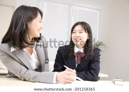 A middle school girl learning from a teacher at an institute