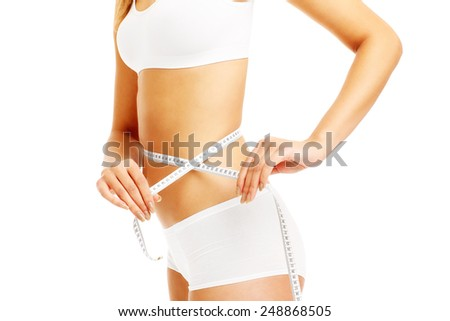 A midsection of a fit woman measuring her waist over white background - stock photo