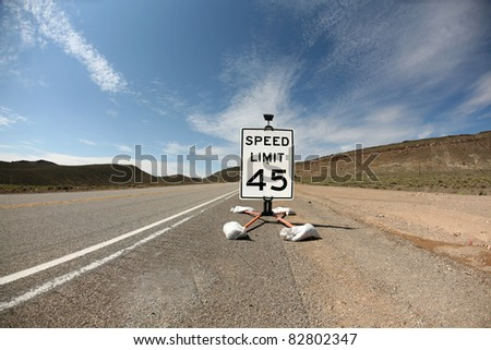 a 45 mile per hour speed limit sign on a highway in the desert. shot with a fisheye lens for a fun distorted image - stock photo