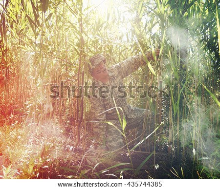 A military army man is in pain and injured in a tall grass field outside for a healthcare, trauma or disability concept. - stock photo