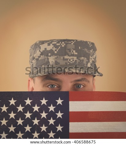A military army soldier is holding an American flag up to his face with a uniform on and copyspace for a veteran, memorial or hero concept. - stock photo