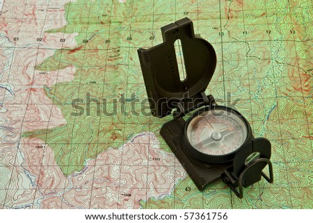 A military compass on a military map. - stock photo