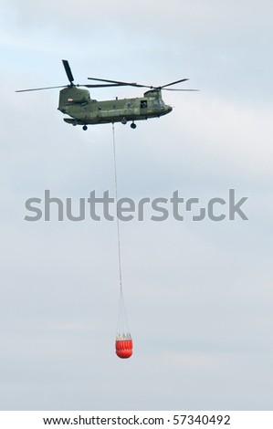 a military helicopter with water-bag - stock photo