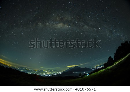 A milky way on above a city in Wonosobo, Indonesia. Mount Sindoro and Mount Sumbing in the foreground.