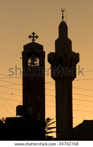 A minaret of the King Hussein Mosque and the steeple of the Coptic Orthodox Church silhouetted on the Amman skyline. - stock photo