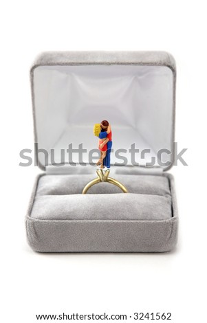 A miniature couple is hugs and kisses inside an engagement ring where the diamond would normally be. The ring is in a velvet ring box. This could be used for a marriage, engagement or love concept. - stock photo