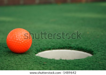 A miniature golf ball near the hole - stock photo