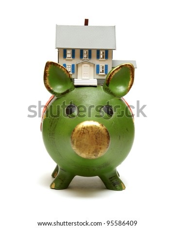 A miniature house rests on a piggy bank for monetary concepts. - stock photo