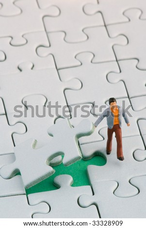 A miniature man is lifting a jigsaw puzzle piece - stock photo