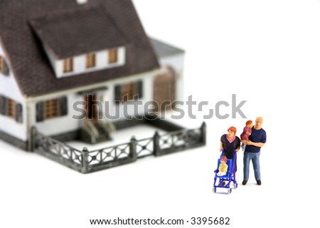 A miniature model home with a family in front. The focus is on the family and the home is out of focus due to shallow depth of field. Isolated on white background. - stock photo
