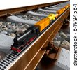 A miniature model of the train - a steam locomotive, railway wagons, tank, platform with sand - on a full-scale rail. - stock photo