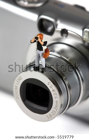 A miniature photographer holding a camera is standing on a full-sized camera. Photography concept. - stock photo