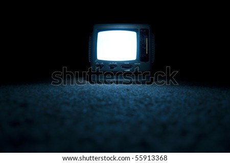 A miniature portable TV screen on at night on the floor with a white screen glowing - stock photo
