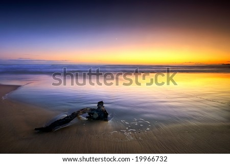 A minimal seascape with a driftwood on the sand under a colorful sunset - stock photo