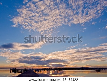 a mirror image of sunset at a marina with a dramatic cloudscape - stock photo