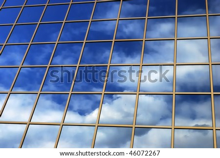 a mirror reflection of sky and clouds is in the windows of building