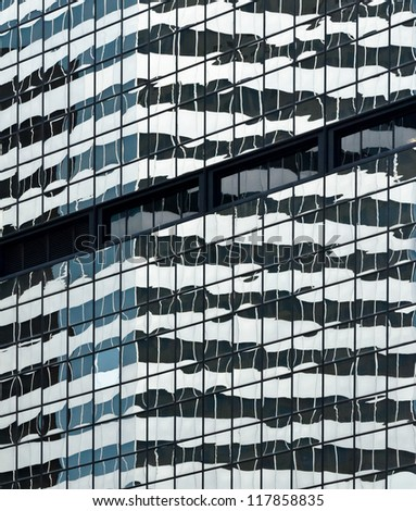 A mirrored building reflecting another building in a downtown city. - stock photo